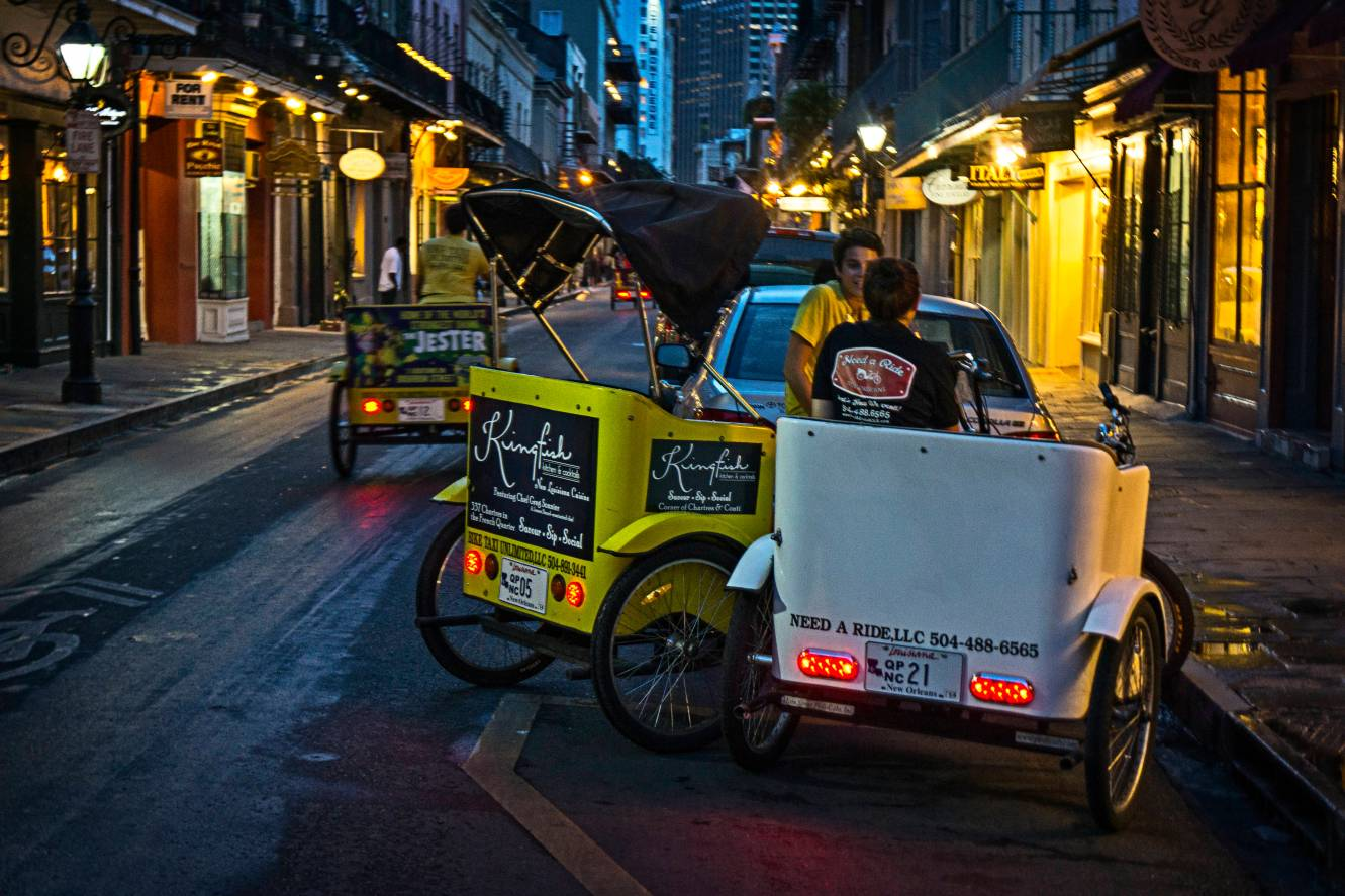 A French Quarter traffic jam. Pedicab drivers take a meeting.