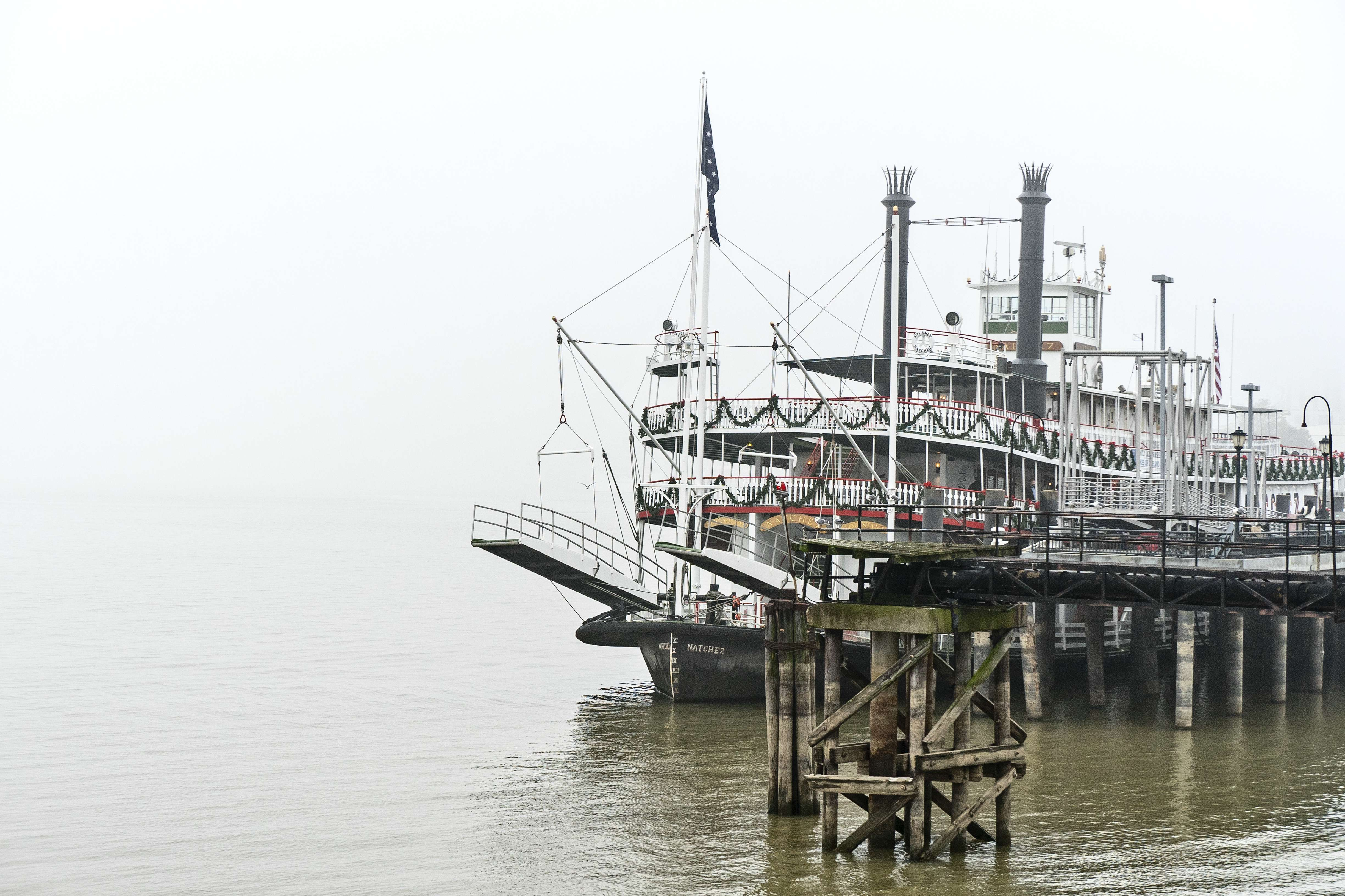 The Natchez steamboat at the foot of The Mississippi River in the fog.