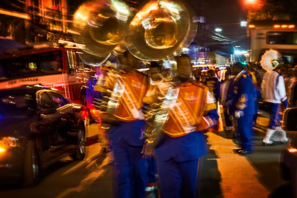 Marching bands walk through crowded streets to reach their place in a Mardi Gras Parade.