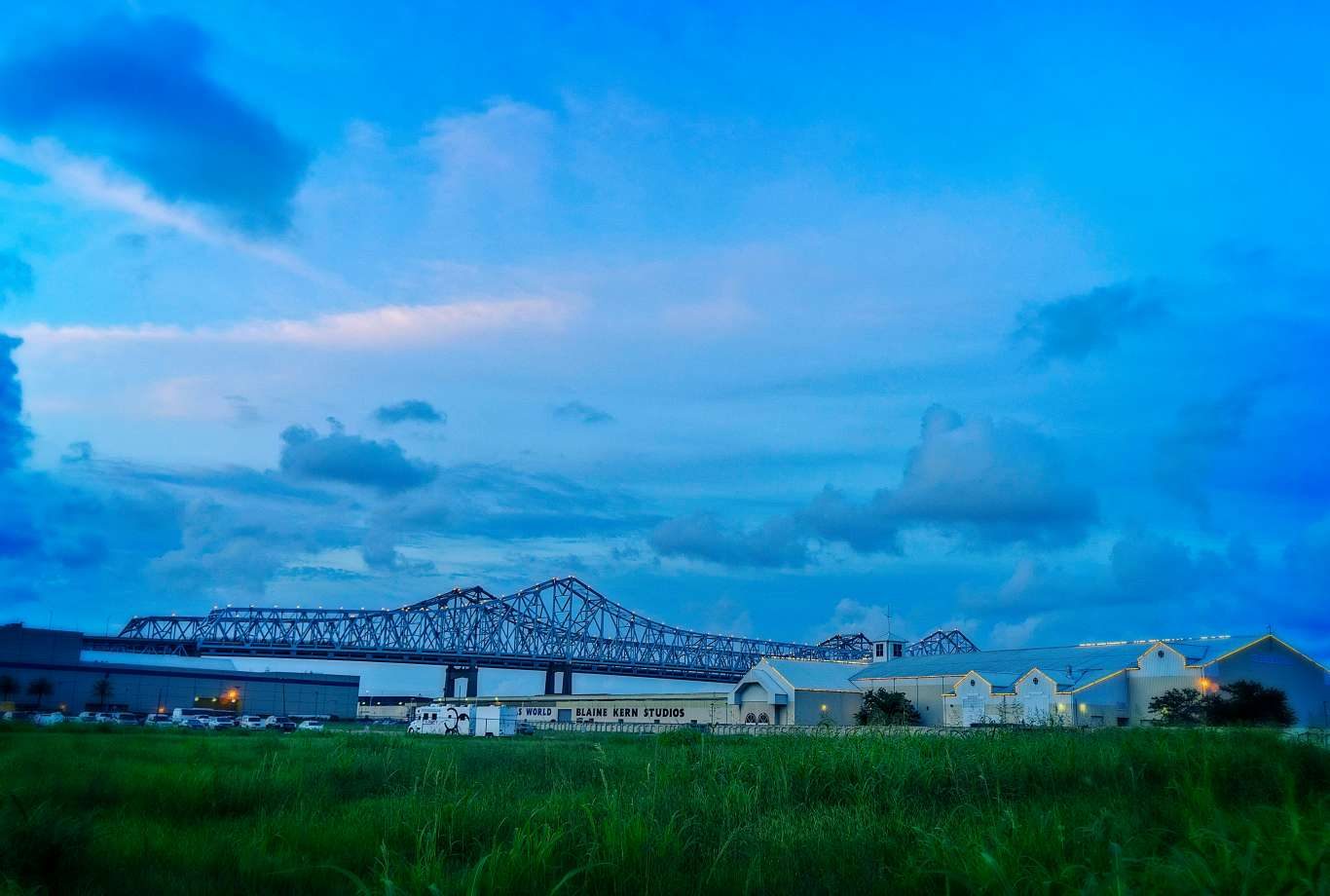 The Crescent City Connection and Mardi Gras World at dusk in New Orleans.