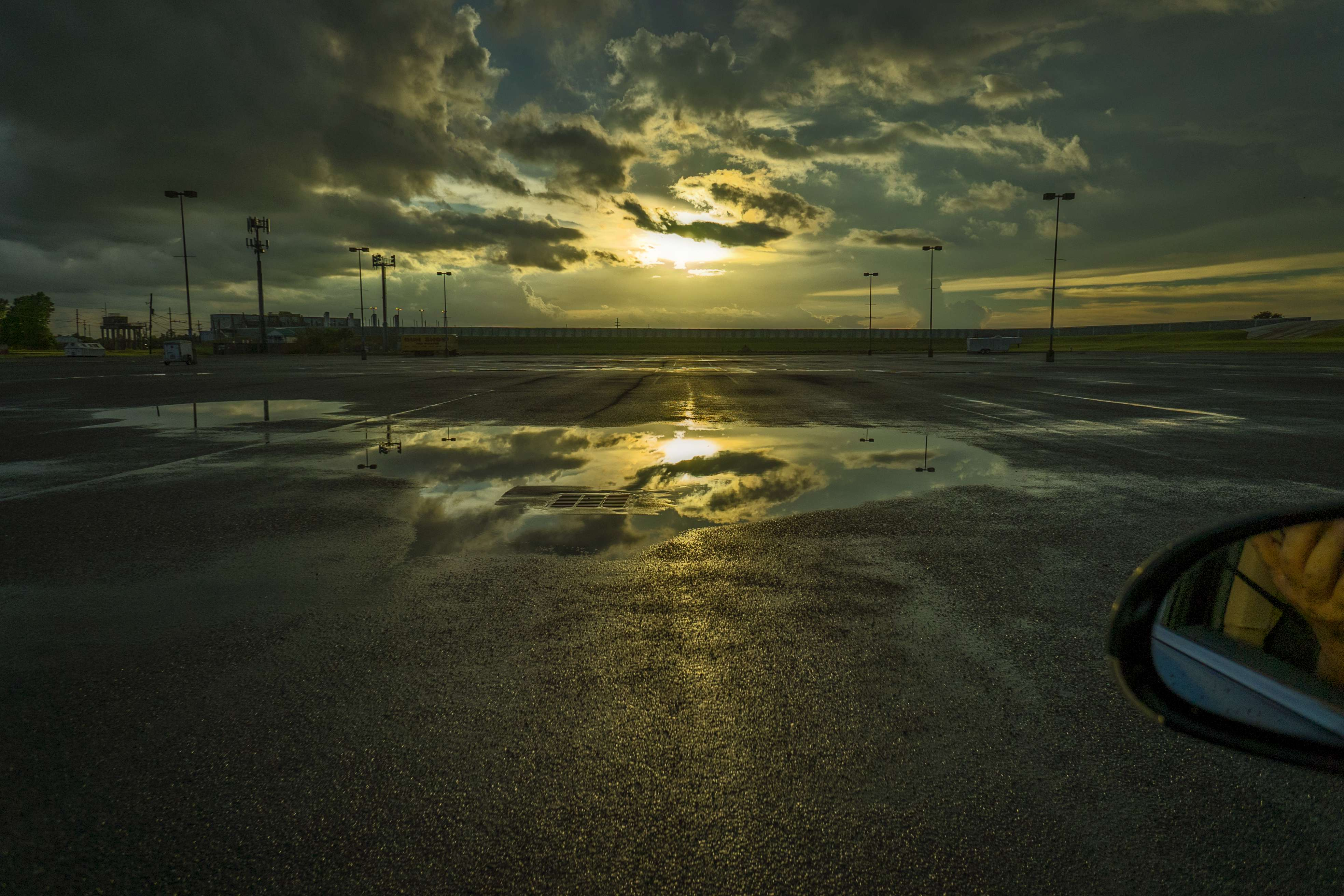 A giant parking lot, storm water and a sunset.