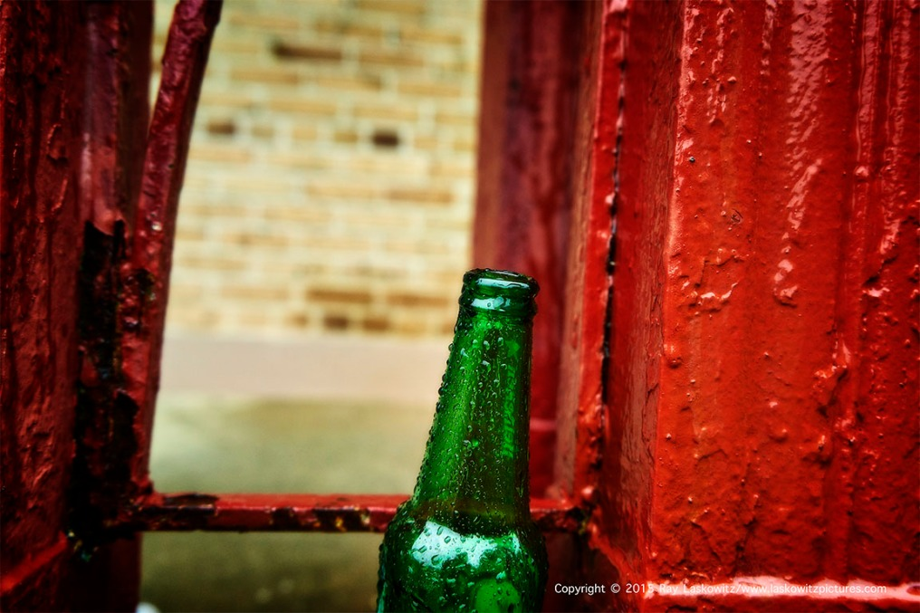 Found art. A Heineken beer bottle and red pasted rail make everyday seem like Christmas. Or not.