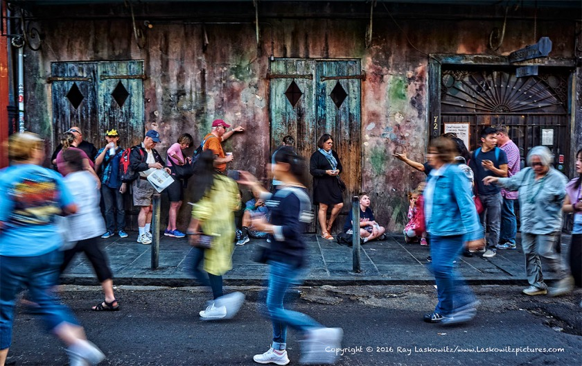 Crowds walking through the French Quarter in New Orleans.