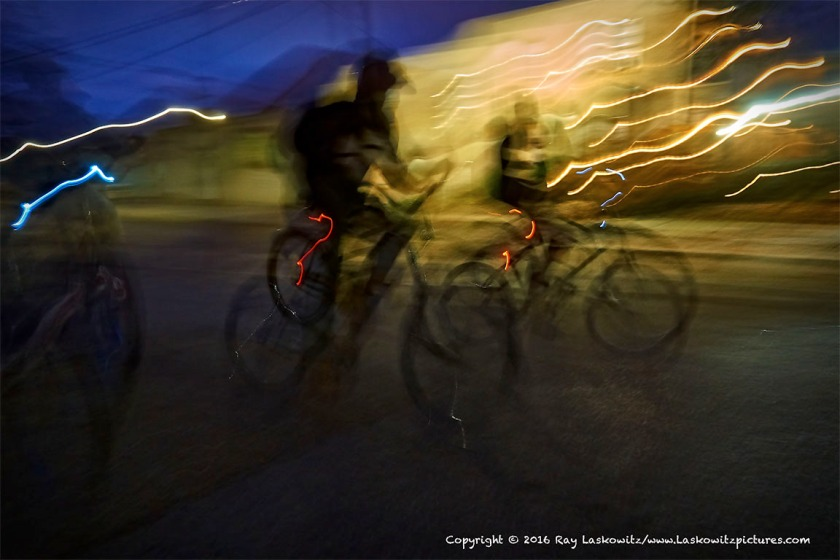 Bicyclists riding through the light.