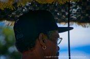 Under his parasol.